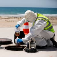 Employees of a wastewater management technology firm demonstrate sewer surveillance, which aims to pinpoint unknown COVID-19 outbreaks, in Ashkelon, southern Israel. | REUTERS