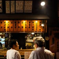 People eat at an izakaya Japanese-style bar in Tokyo on Saturday. | AFP-JIJI