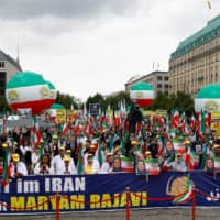 Supporters of Iranian opposition leader Maryam Rajavi and the National Council of Resistance of Iran (NCRI) gather to protest against the death penalty in Iran in front of the Brandenburg Gate in Berlin. | REUTERS