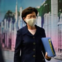 Hong Kong Chief Executive Carrie Lam leaves after a news conference on Friday.  | AFP-JJJI