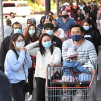 Shoppers wait in a long line outside a Costco in Melbourne on Sunday ahead of a government announcement about a new COVID-19 lockdown.   | AFP-JIJI