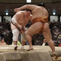 Terunofuji (left) pushes out Mitakeumi to win his bout and clinch the title on the final day of the July Grand Sumo Tournament on Sunday at Ryogoku Kokugikan. | KYODO