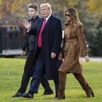 U.S. President Donald, first lady Melania Trump, and their son, Barron, walk to board Marine One on the South Lawn of the White House in Washington last November. | AP