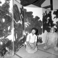 Toshi (left) and Iri Maruki, seen here in front of one of their panels in 1972, began painting the works after visiting Hiroshima in the aftermath of the 1945 bombing. | KYODO