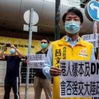 Pro-democracy district councilor Lui Man-kwong (right) protests outside the Hospital Authority headquarters in Hong Kong on Sunday against the government's decision to have mainland inspectors carry out COVID-19 testing in the city.   AFP-JIJI