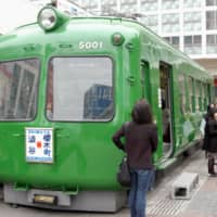An old train car, nicknamed 'green frog,' served as a tourist information center outside Tokyo's Shibuya Station. | KYODO