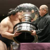 Terunofuji receives a trophy from JSA Chairman Hakkaku after winning the July Basho on Sunday | KYODO