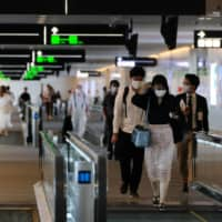 Passengers head to their respective departure gates at the domestic terminal of Tokyo's Haneda Airport on July 25. | AFP-JIJI