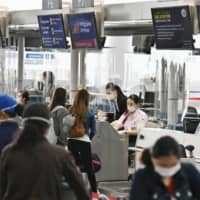 People wait before check-in counters at Chubu Centrair International Airport in Tokoname, Aichi Prefecture, on June 17 as the airport resumed some international flights.