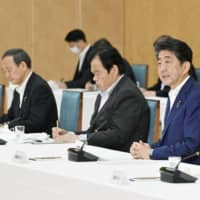 Prime Minister Shinzo Abe, right, attends a meeting at the Prime Minister's Office on Monday.  | KYODO