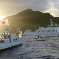 A Chinese vessel (right) sails near the Senkaku Islands in 2013. | KYODO