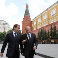 Then-Russian President Dmitry Medvedev walks with then-Prime Minister Vladimir Putin after a remembrance ceremony at the Tomb of the Unknown Soldier in Moscow in 2011.  | REUTERS