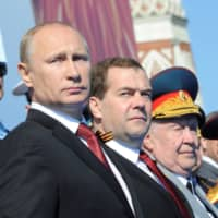Russian President Vladimir Putin and Prime Minister Dmitry Medvedev watch the Victory Day parade in Moscow's Red Square in 2014.  | KREMLIN VIA / REUTERS