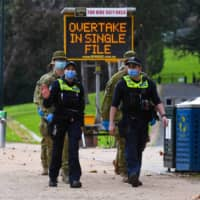 Police officers and soldiers patrol a popular running track in Melbourne on Tuesday after the state announced new restrictions as the city battles fresh outbreaks of the COVID-19 coronavirus.  | AFP-JIJI