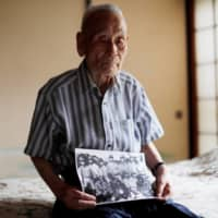 Lee Hak-rae, the last surviving Korean war criminal from World War II, holds a copy of a photo that was taken at a POW camp run by the Japanese Imperial Army in Thailand in 1942, during an interview at his home in Tokyo.  | REUTERS