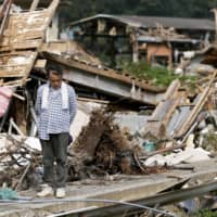 A man prays for victims in Kuma, Kumamoto Prefecture, on Tuesday, one month after torrential rain killed dozens in Kyushu. | KYODO