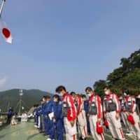Kuma village officials offer a silent prayer and the Japanese flag is flown at half-mast at the municipal government office on Tuesday. | KYODO