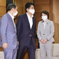 Prime Minister Shinzo Abe and Chief Cabinet Secretary Yoshihide Suga attend a Cabinet meeting in Tokyo on Tuesday. | KYODO