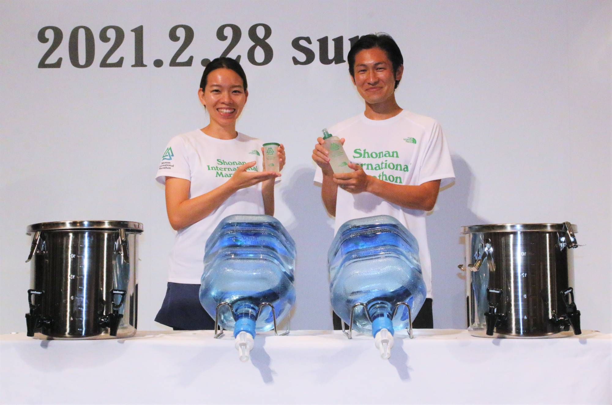 Models pose with the reusable cup and bottle that runners will carry with them during the Shonan International Marathon at a news conference in Tokyo on Tuesday. | KAZ NAGATSUKA