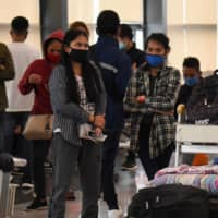 Stranded domestic flight passengers wait for updates at the airport in Manila on Tuesday after all domestic flights were canceled following new restrictions to combat the COVID-19 outbreak.   | AFP-JIJI