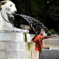 A tourist cools off at the Barcaccia fountain by the Spanish Steps in central Rome on Saturday amid a heat wave.  | AFP-JIJI