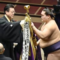 No. 17 maegashira Terunofuji receives the champion flag from his stablemaster Isegahama after winning the July Grand Sumo Tournament on Sunday at Ryogoku Kokugikan. | KYODO