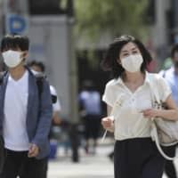 People wearing face masks to help protect against the spread of the new coronavirus walk on a street in Tokyo. | AP