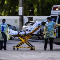 Medics transfer a patient on a stretcher from an ambulance outside of a hospital near Miami.  | AFP-JIJI