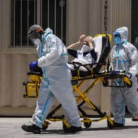 Medics transfer a patient on a stretcher from an ambulance outside of a hospital near Miami.    AFP-JIJI