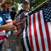 Protestors hand out American flags outside of the Ohio Statehouse during a right-wing protest against mask-wearing last month in Columbus.  | AFP-JIJI