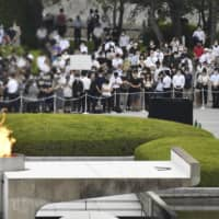 People offer a silent prayer at 8:15 A.M., the exact time an atomic bomb was dropped on Hiroshima 75 years ago, during a ceremony to mark the anniversary at the Hiroshima Peace Memorial Park on Thursday. | KYODO