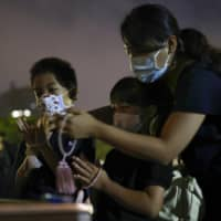 People offer prayers before dawn on Thursday at the Hiroshima Peace Memorial Park, on the 75th anniversary of the atomic bombing on the city. | KYODO