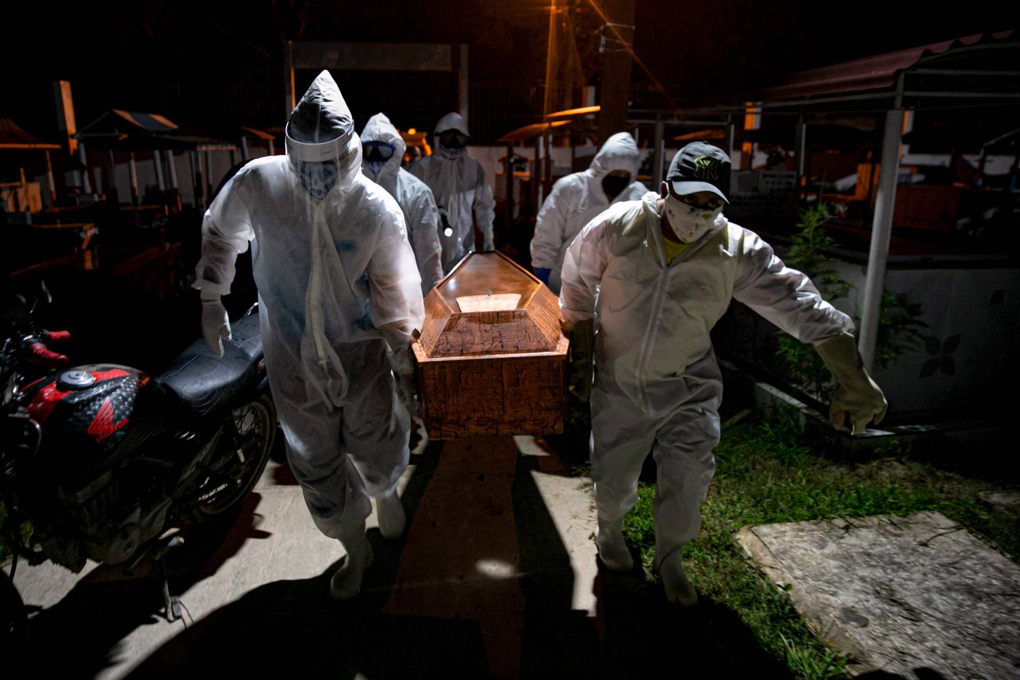 Gravediggers wearing protective clothing carry the coffin of a victim of the coronavirus for its burial at a cemetery in Breves, Brazil. | AFP-JIJI