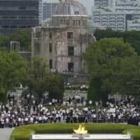 Visitors observe a minute of silence for victims of the atomic bombing at 8:15 A.M., the time the atomic bomb exploded over Hiroshima, during a ceremony Thursday at the Hiroshima Peace Memorial Park to mark the 75th anniversary of the bombing. | AP