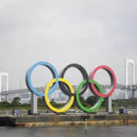 The Olympic rings are pulled out of Tokyo Bay by a barge on Thursday. The monument is being taken away for safety inspections. | AP