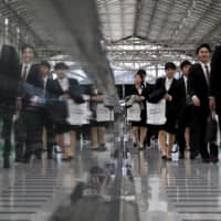 Job seekers walk towards a job fair held for fresh graduates in Tokyo in March 2016.  Job offers to students set to graduate from universities next March fell 15.1 percent from a year earlier amid the coronavirus pandemic, logging the sharpest drop in a decade. | REUTERS