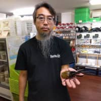 Akio Ohara, seen holding a Hercules beetle, says business has been good recently, despite having closed his shop during the state of emergency. | ANDREW MCKIRDY