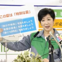 Tokyo Gov. Yuriko Koike holds up a sign asking people to refrain from going back to their hometown or travel during the Bon holiday while giving a news conference at the metropolitan government building Thursday. | KYODO
