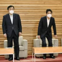 Prime Minister Shinzo Abe and other ministers are pictured before a Cabinet meeting at the Prime Minister's Office on Friday. | KYODO