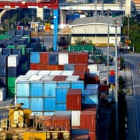 Containers are stacked at Tanjung Priok port in Jakarta. Indonesia announced in June that seven foreign companies would relocate their plants from China to Indonesia, including three from Japan. | REUTERS