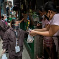 Government workers in hazmat suits sell fresh produce amid the reimposed lockdown to curb the spread of the coronavirus in Navotas, Metro Manila. President Rodrigo Duterte's government loosened restrictions too soon, without ensuring that local officials could trace and treat infections, said Anthony Leachon, an internist at the Manila Doctors Hospital. | REUTERS