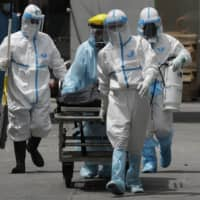 Health workers in protective suits transport a corpse at a hospital in Manila on Thursday.  | AP