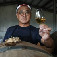 Chen Chien-hao, 52, holds a glass of his wine at Shu Sheng Leisure Domaine in Taichung, Taiwan.  | REUTERS