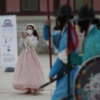 Visitors hold smartphones while maintaining social distancing during a re-enactment ceremony of the changing of the Royal Guard at Gyeongbok Palace in Seoul last month. | AP
