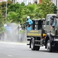 A soldier sprays disinfectants on a road from a military vehicle to help curb a coronavirus outbreak in Da Nang, Vietnam, on Aug. 3. | REUTERS