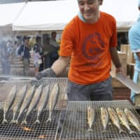 A man grills saury in the town of Onagawa, Miyagi Prefecture, in September last year.  | KYODO