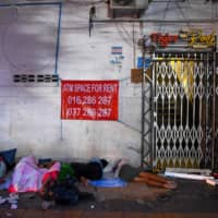 Homeless people sleep on a sidewalk in Phnom Penh. Underprivileged people in cities are particularly vulnerable as they often live in densely populated areas where social distancing is hard, especially if they have to share a water source. | AFP-JIJI
