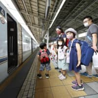 Passengers with children board a bullet train at JR Shin-Osaka Station on Saturday morning. | KYODO