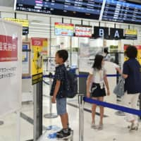 A boy has his body temperature checked at Osaka Airport on Saturday.  | KYODO