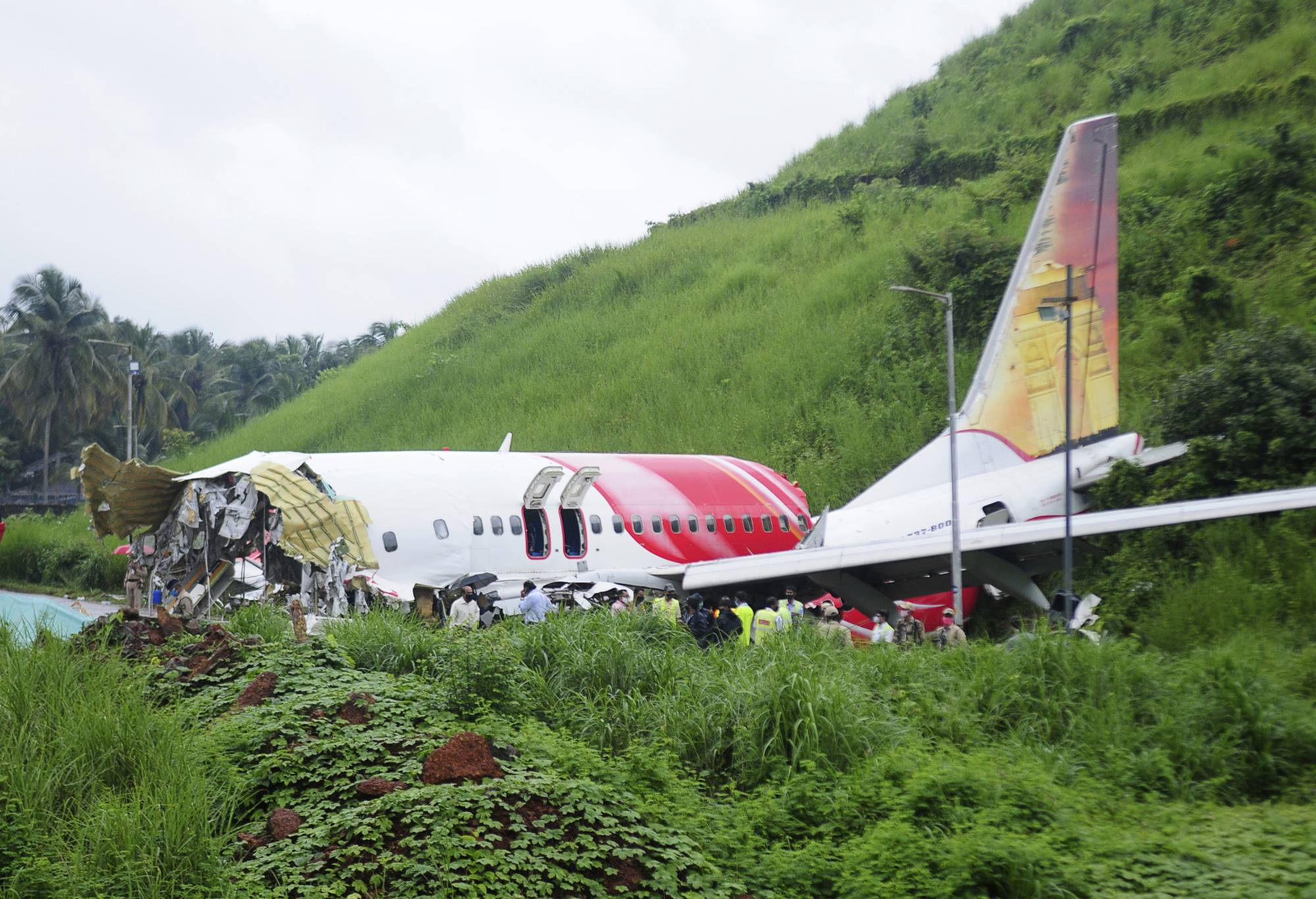 Officials stand Saturday on the debris of the Air India Express flight that skidded off a runway while landing in Kozhikode, Kerala state, India. | AP
